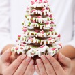 Woman and child hands holding gingerbread decorated christmas tr — Stock Photo