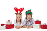 Happy kids with elf and reindeer hats laying among presents — Stock Photo