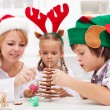 Family decorating the gingerbread christmas tree — Stock Photo #15038529