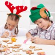 Santa little helpers decorating gingerbread cookies — Stock Photo #15038649