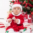 Baby girl in front of christmas tree — Stock Photo