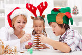 Family decorating the gingerbread christmas tree — Stock Photo