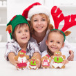 Family in christmas hats making gingerbread cookie - Stock Photo