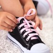 Child ties shoe - closeup - Stockfoto