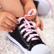 Child ties shoe - closeup - Stock Photo