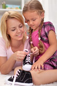 Mother teaching child how to tie shoes — Stock Photo