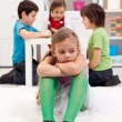 Stock Photo: Sad little girl sitting excluded by the other kids