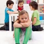 triste ragazza piccola seduta esclusi da altri bambini — Foto Stock