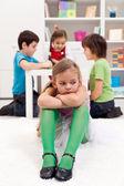 Ledsen liten flicka sitter inte omfattas av de andra barnen — Stockfoto