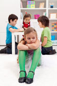 Sad little girl sitting excluded by the other kids — Stock Photo
