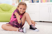 Little girl learning how to tie her shoes — Stock Photo