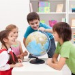 Kids looking at earth globe — Stok fotoğraf