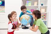 Kids looking at earth globe — Stock Photo