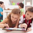 Little girls playing on a tablet computing device — Stok fotoğraf