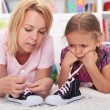 Mother teaching little girl to tie her shoes — Stock Photo