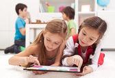 Små flickor spelar på en tablet datorenhet — Stockfoto