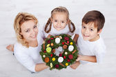 Woman with two kids holding advent wreath — Stock Photo