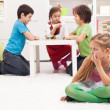Little girl sitting apart - feeling excluded by the others - Stock Photo
