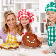 Little chef girls with their mother making a cake — Stock Photo