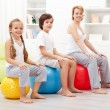 Kids exercising with their mother - Stock Photo