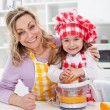 Happy woman and child making fresh orange juice — Stock Photo
