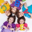 Happy school kids with colorful alphabet letters — Foto de Stock