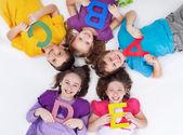 Glückliche kinder mit bunten buchstaben — Stockfoto