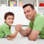 Постер, плакат: Father arm wrestling with his boy