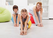 Happy family doing stretching exercises at home — Stock Photo