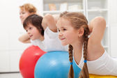 Kids and woman doing exercises with balls — Stock Photo