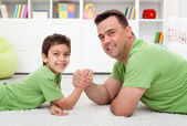 Father arm wrestling with his boy — Stock Photo