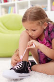 Little girl ties shoes — Stock Photo