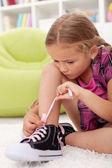 Little girl ties shoes — Stock Photo