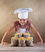 Little chef with pasta variety in bags — Stock Photo