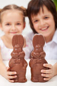 Happy easter kids with large chocolate bunnies — Stock Photo