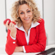 Woman at the office holding apple — Stock Photo #22283635