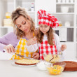 Mother and little girl making a cake together — Stock Photo #22283999