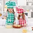 Little girls with chef hats preparing a cake — Stock Photo
