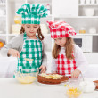 Little girls with chef hats preparing a cake — Stock Photo #22284077