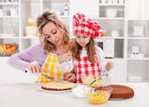 Mother and little girl making a cake together — Stock Photo