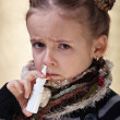 Little girl with the flu using nasal spray - Stock Photo