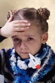 Little girl with the flu checking her temperature — Stock Photo