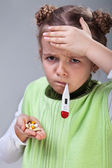 Sick little girl with pills and thermometer — Foto Stock