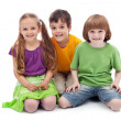 Happy kids sitting on the floor — Stock Photo #23482325