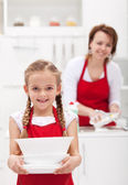 Little girtl helping mother to do the dishes — Stock Photo