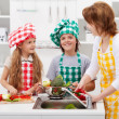 Woman and kids washing vegetables in the kitchen — Stock Photo