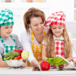 Woman and kids preparing the vegetables for a meal — Stock Photo #25388003