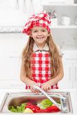 Lilla kocken tvätta grönsaker — Stockfoto