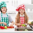 Kids helping in the kitchen - washing and slicing vegetables — Stock Photo