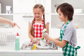 Do the dishes - kids ordered to help in the kitchen — Stock Photo